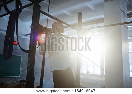 Portrait of bald bearded man performing pull ups on bar during workout in gym lit by sunlight with lens flare