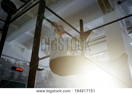 Low angle portrait of strong bearded man performing straight leg chin ups on bar during workout in gym lit by sunlight