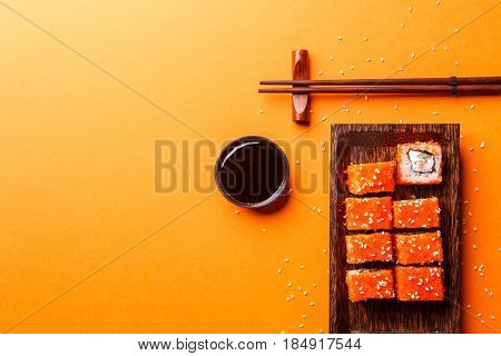 Photo of rolls, sticks, soy sauce on empty orange background