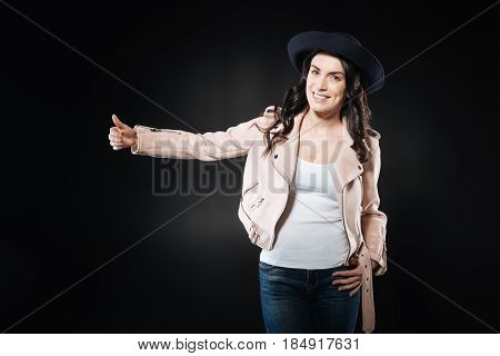 Spring time. Lovely nice young woman standing against black background while touching her waist, gazing into camera.