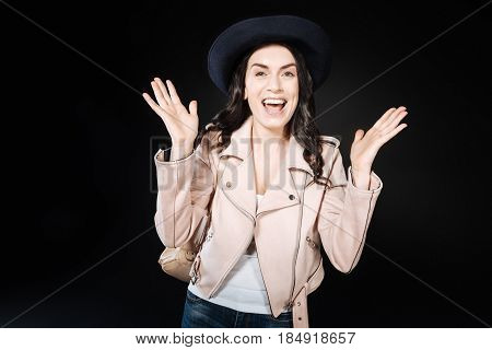 Feeling happiness. Delighted pretty woman holding her hands upwards looking forward while feeling good emotions