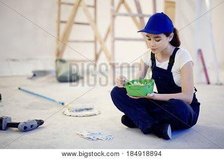 Portrait of young woman wearing workers uniform sitting cross legged on floor in construction site having lunch break
