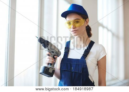 Portrait of young confident woman posing with power drill and smiling while installing windows on construction site