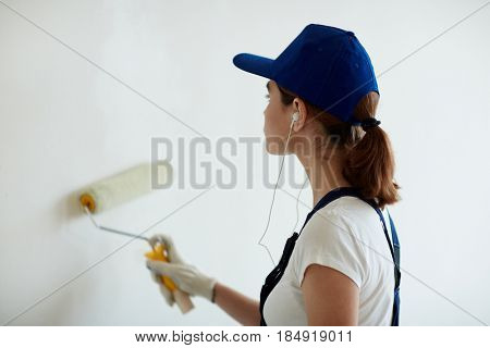Rear view portrait of young woman on construction site: female worker painting walls white using paint roller  while remodeling office and listening to music