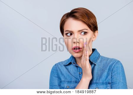 Young Beautiful Red Hair Girl Is Telling Someone A Secret And Looks Shocked. She Is Dressed In Jeans