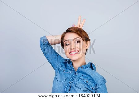 Playful Young Cute Girl Is Making Herself Horns With Fingers On Light Blue Background