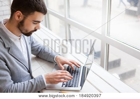 Young bearded trader analyzing financial market via laptop while sitting at panoramic window of coffeehouse, profile portrait shot