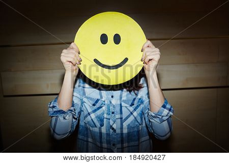 Successful female designer expressing happiness with help of smiling emoji mask while standing in dim room, waist-up portrait