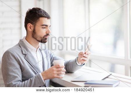 Calm businessman having coffee break in cozy cafe: he sitting at panoramic window with paper cup in hand and texting with his friend, waist-up portrait