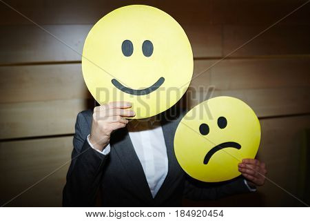 Waist-up portrait of unrecognizable white collar worker hiding her face under smiling mask and holding sad one in hand while standing in dim room