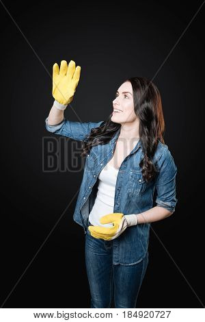 Relax time. Attractive female with curly locks wearing casual clothes using rubber gloves while going to work in the garden