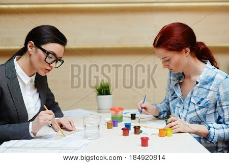Left-brained and right-brained women at work: pretty architect in formalwear working on project while her colleague in casualwear creating picture with brush and gouache, profile view