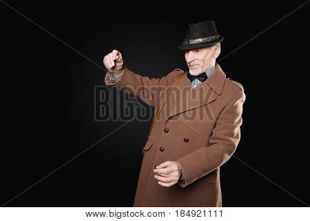 Time to read. Attentive male person wearing black hat and stylish coat keeping his mouth opened while holding hands in the air