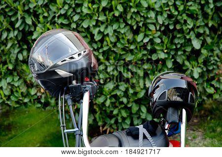 Moto helmet on motorcycle handlebars and motorbikes on blurred background