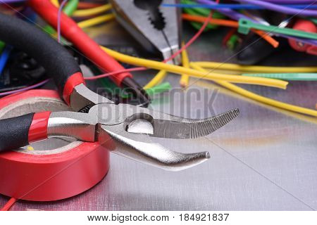 Set of electrical tools and components on metal background