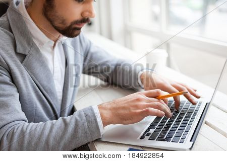 Close-up shot of bearded businessman typing response email to his client on laptop while having coffee break in cafe