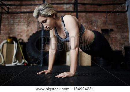 Attractive blond-haired sportswoman doing push-ups during intensive fitness training in gym, full-length portrait