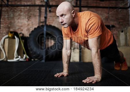 Handsome middle-aged sporty man wrapped up in intensive training: he flexing muscles while doing push-ups in gym, full-length portrait