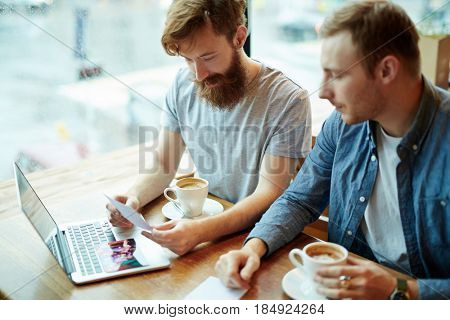 Two young bearded friends gathered together in cozy coffeehouse and looking through printed photos with interest, waist-up portrait
