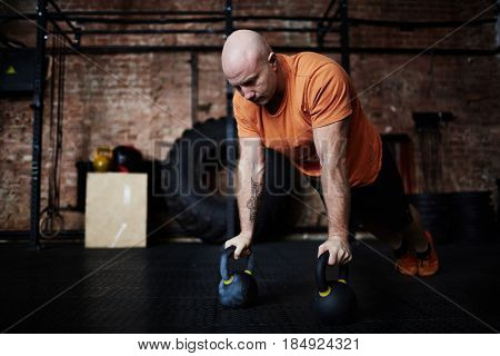 Middle-aged sportsman doing push-ups with kettlebells during intensive workout in modern gym, full-length portrait