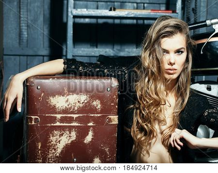 girl or sexy woman fashion model with curly blond long hair in unbutton erotic black shirt with vintage suitcase sitting on floor on motorcycle garage background. Traveling and vacations