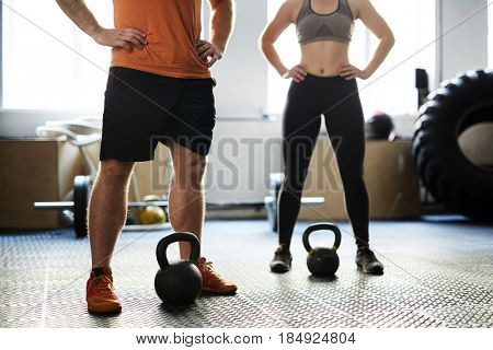 Unrecognizable man and woman having fitness training with kettlebells in gym