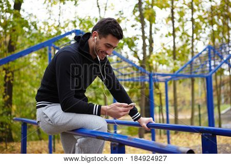 Smiling young sportsman listening to music on smartphone while sitting on parallel bars in autumn park, full-length portrait