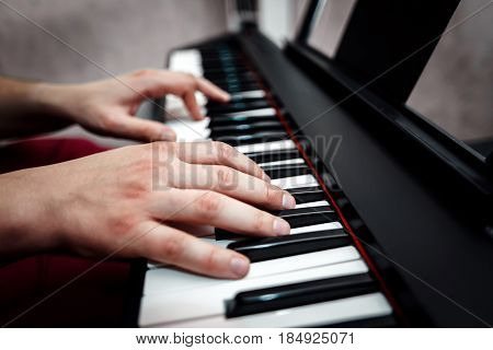 the pianist plays the piano. The pianist's hands closely. the view from the top