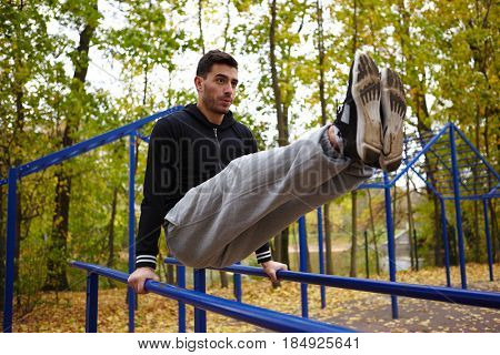 Handsome bearded man doing triceps dips on parallel bars while having outdoor workout, full-length portrait