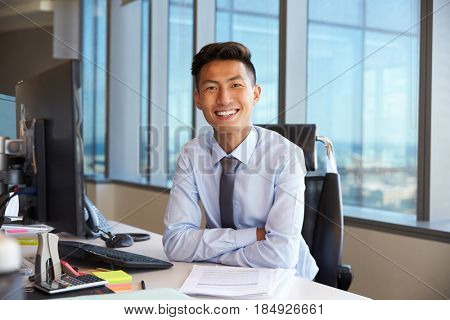 Portrait Of Young Businessman At Office Desk Using Computer