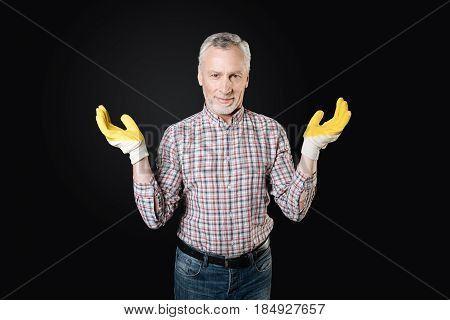 I do not know. Enigmatical male person keeping smile on his face keeping hands bent in elbows while posing on camera
