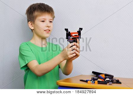 The boy shows the robot which he made from the set for construction