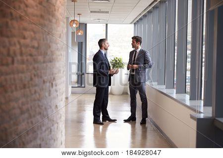 Two Businessmen Having Informal Meeting In Office Corridor