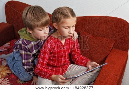 Satisfied children are watching video on tablet computer