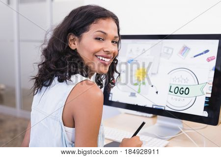 Smiling businesswoman using desktop computer while working at desk in office