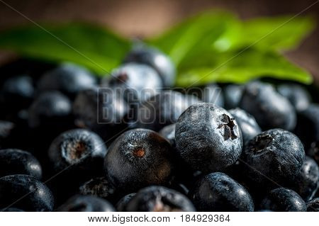 blueberries on wooden background Freshly blueberries in wooden bowl. Juicy and fresh blueberries with green leaves on wood table. Blueberry antioxidant. Concept for healthy eating and nutrition