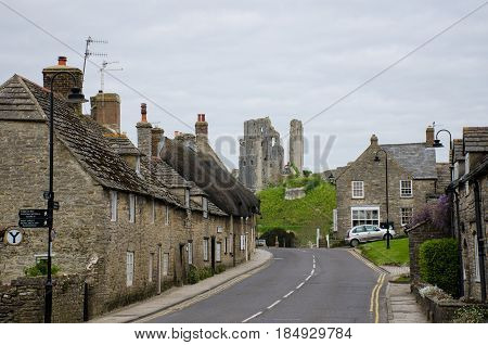 Corfe Castle Dorset United Kingdom -23 April 2017: Corfe village main street with castle in background