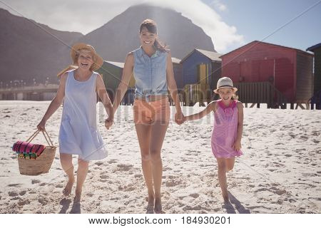 Portrait of multi-generated family walking at beach during sunny day