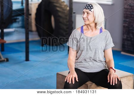 Staying fit. Joyful sporty elderly woman sitting and having a short rest while working out in the gym