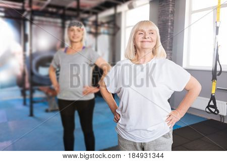 Great mood. Happy active elderly woman resting hands on her hips and doing a physical exercise while enjoying the activity