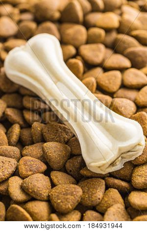 Dry kibble dog food and chew bone.