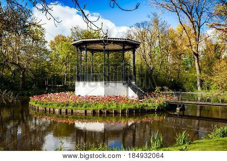 Pond with beautiful rotunda arc and tulips in Vondelpark in Amsterdam, Netherlands