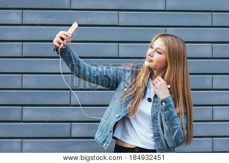 beautiful stylish women making selfie. happy young blonde girl listening to music and making selfie on a blue background.