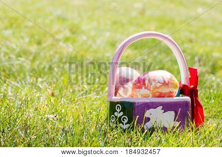 basket filled with tie dyed easter eggs sitting outside on grass