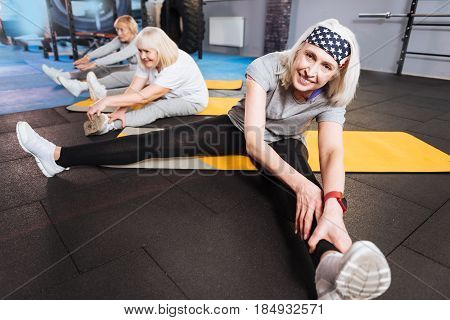 Active lifestyle. Positive happy active woman sitting on the yoga mat and trying to do the splits while stretching