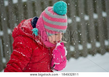 Adorable school age girl eating snow outside in wintertime