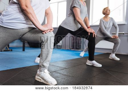 Simultaneous movements. Nice positive elderly women putting their legs forward and doing a physical exercise while standing in a row