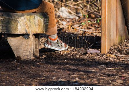 Close up of toddler boy's leg and shoe while sitting on log outside in wintertime