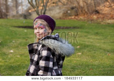Adorable school age girl with facepaint playing outside in wintertime