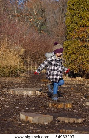 Adorable school age girl playing outside in winter coat and hat